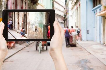 tourist taking photo of old street in Havana