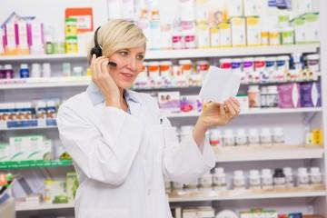 Pharmacist with headphone reading a prescription