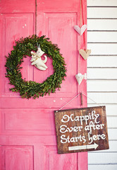 Valentine wreath and sign board on wooden vintage pink door
