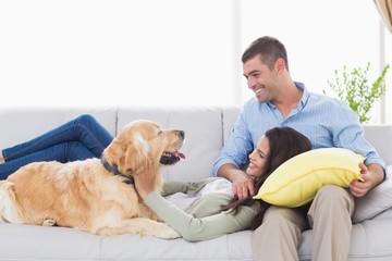 Couple with dog on sofa