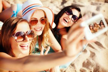 girls making self portrait on the beach