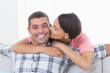 Happy man being kissed by woman