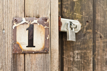 Hausnummer 1 auf einem Bretterzaun neben einem Vorhängeschloss