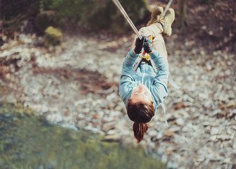 Woman crossing a river with tyrolean traverse