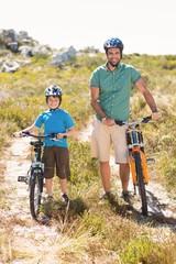Father and son biking through mountains