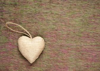 Heart shape hanging ornament against pink green woolen blanket