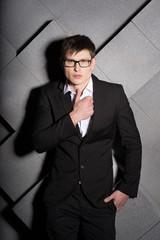 Handsome elegant man in black suit with glasses. Success