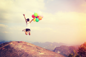 young asian woman mountain peak jumping with colored balloons