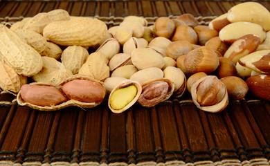 Nuts in line-peanuts,walnuts,pistachios,brasil nuts on brown mat