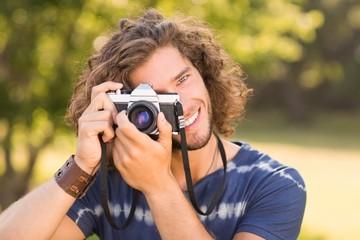 Handsome hipster using vintage camera