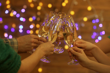 Clinking glasses of champagne in hands on lights background