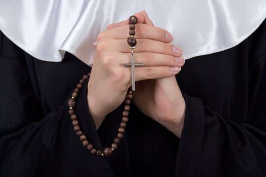 close up of rosary in nun hands