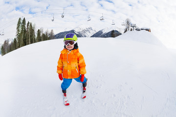 Small boy in ski mask and helmet skiing alone