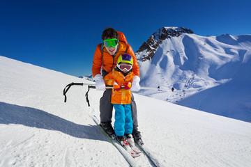 Father give mountain ski lesson to little boy