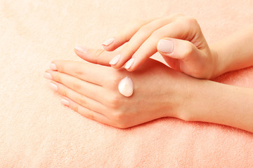 Woman caring hands with cream on fabric background