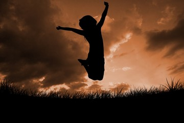 Composite image of silhouette of little girl jumping