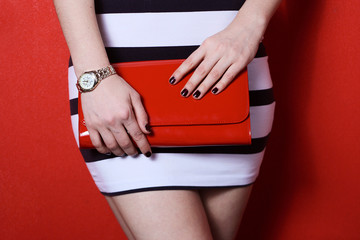 woman in striped black and white skirt holding red handbag