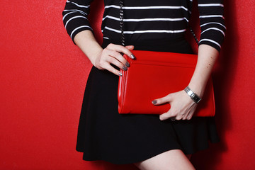 Wall Mural - Trendy young woman holding  red leather handbag
