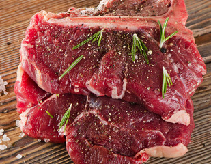 Raw T-Bone Steak with Seasoning and Rosemary on  wooden board.