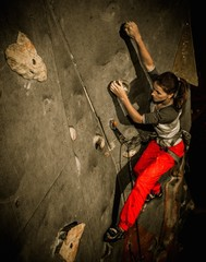 Young woman practicing rock-climbing on a rock wall indoors
