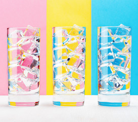 Three glasses on colorful background.