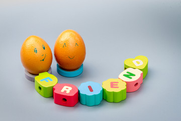 friendship concept : two eggs with friend letters on color wood