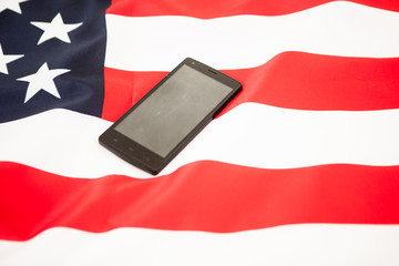 Black smartphone on the flag of the United States