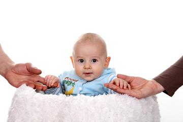 Uśmiechnięte niemowlę z dłońmi rodziców.