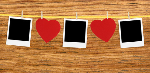 Vintage photos frame on the clothesline with hearts over wooden