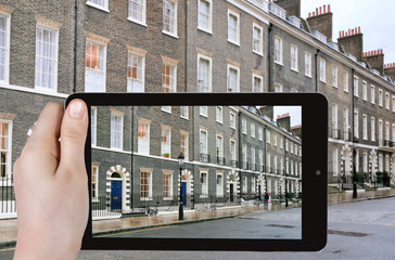 tourist taking photo of houses in London