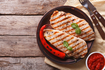 Grilled chicken fillet and chili on a plate horizontal top view