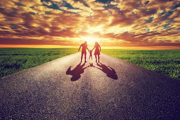 Family walk on long straight road, way towards sunset sun