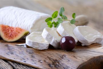 Gereifte Ziegenkäserolle mit Feigen und Oliven