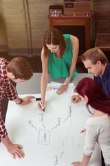 junge leute arbeiten zusammen an einem chart