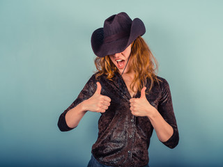 Woman wearing cowboy hat giving thumbs up