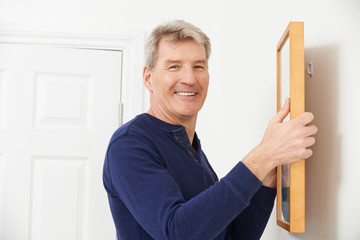Mature Man Hanging Picture On Wall