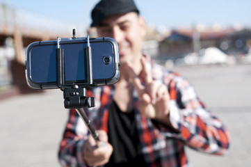 young man taking a selfie with a monopod