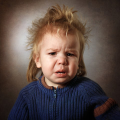 portrait of a frustrated baby on a dark background