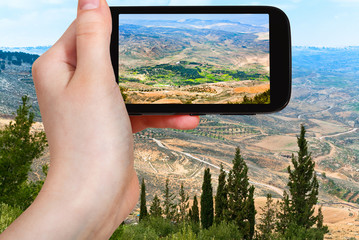 tourist taking photo of Holy Land from Mount Nebo