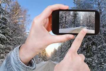 tourist taking photo of winter road in snow forest