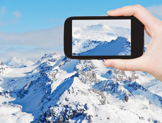 tourist taking photo of snow mountains in Alpes