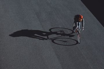 Cyclist is crossing the road and dropping beautiful shadow