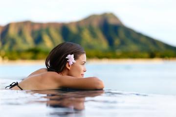 Wall Mural - Infinity pool resort woman relaxing at beach
