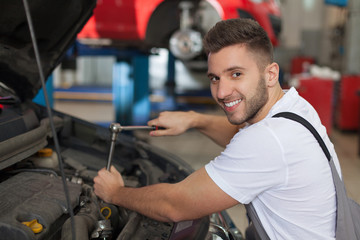 Smiling mechanic using a ratchet wrench