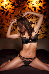 Sexy woman playing with handcuffs in bedroom