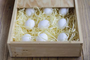 Eggs on a soft substrate in a wooden box.