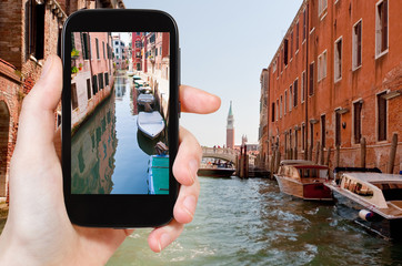 tourist taking photo of Canal and bridge, Venice