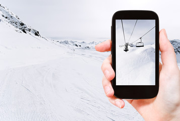 tourist taking photo of skiing tracks and ski lift