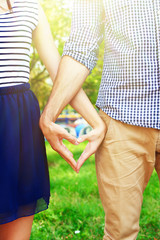 Loving couple holding hands outdoors on sunny nature background