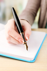 Female hand with pen writing on notebook, closeup